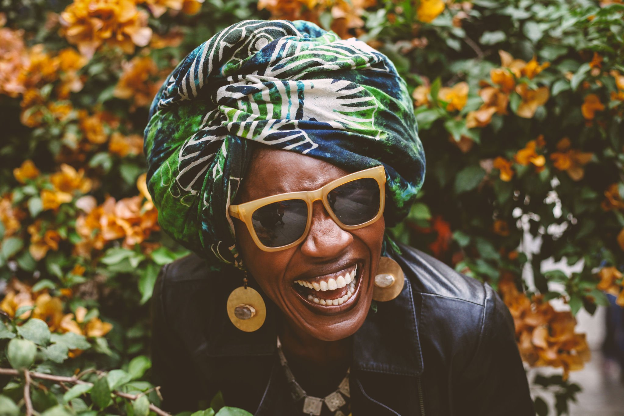 Image of Uchechi Kalu in front of orange bougainvillea. She is wearing orange-framed sunglasses and doubled over with laughter.
